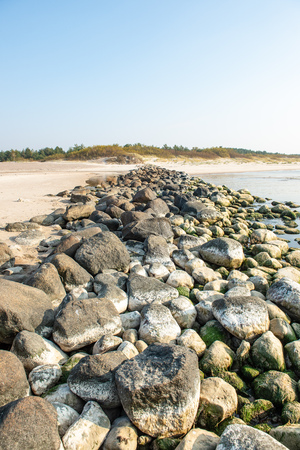 calm sea beach in summer with large rocks and wooden poles from old breakewater in the sea. blue sky