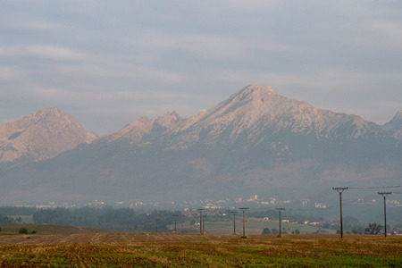 cloudy and foggy sunrise over slovakian landscape in autumn. Tatra moountains in background as the sun rises. Electricity poles in field
