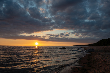 colorful sunset over calm sea beach with dark blue water and dramatic contrasty clouds. rocks in water