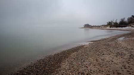 empty sea beach with ice leftovers and no snow in winter 写真素材