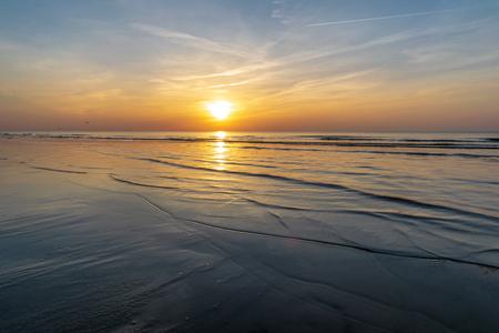 Orabge farbiger Sonnenuntergang über ruhigem Meer Strand Wasserfelder mit schwebenden Wolken