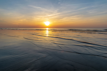 orabge gekleurde zonsondergang over kalme zee strand watervelden met zwevende wolken