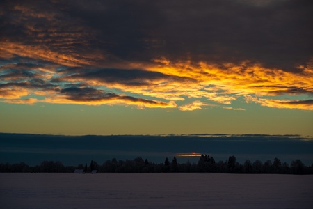 colorful sunset light over fields of snow in winter in countryside 免版税图像