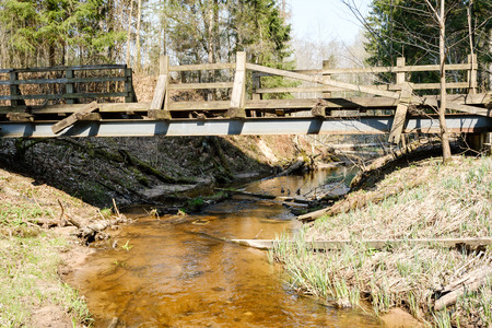bridge over small forest river, sunny spring day Stockfoto