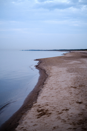calm sea beach on the shore of Baltic sea with blue clouds and low tide, silent water with no waves evening