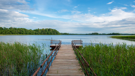 wooden plank foothpath boardwalk trampoline in the lake with blue water in summer