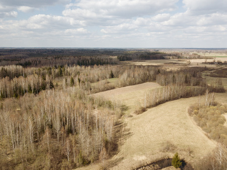 aerial view of countryside fields and forests with small lakes in overcast spring day
