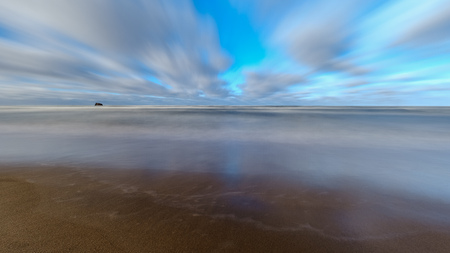 sea beach with sand and water in sunny day. long exposure shoot