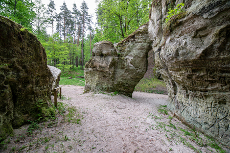 sandstone cave entrance in dark. sand covered ground. latvia