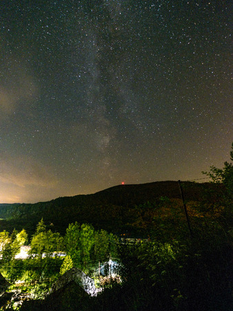 night stars and milky way galaxy above slovakian village at nightfall