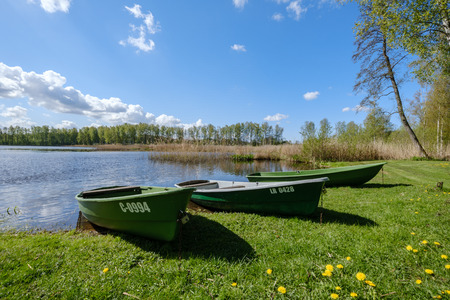 recreation camping area by the blue lake in sunny summer day on the shore of water body with trees, green meadow with dandelions and boats on the shore