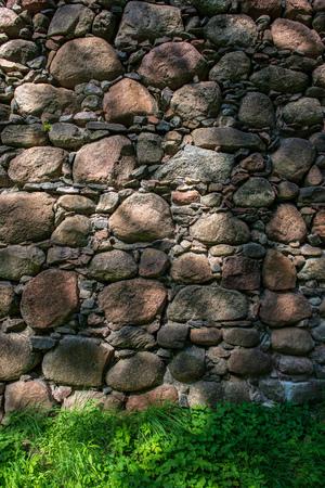 beautiful ancient stone brick wall with green grass below