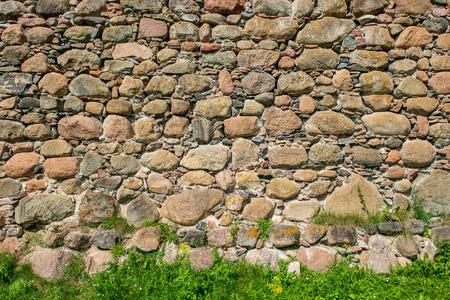 beautiful ancient stone brick wall with green grass below Stockfoto - 122752514