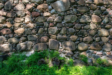 beautiful ancient stone brick wall with green grass below Stockfoto - 122752520