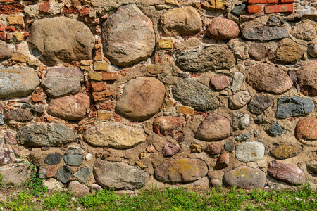 beautiful ancient stone brick wall with green grass below Stockfoto - 122752560
