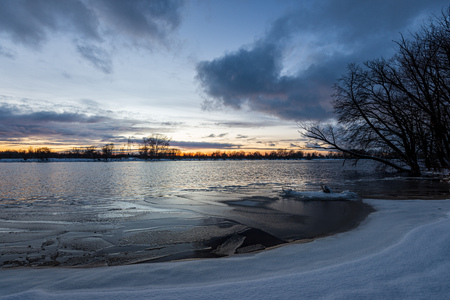 frozen river in winter countryside. ice blocks floating and snow covered shores. latvia