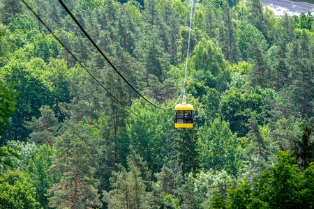 cable car crossing valley of Gauja in Sigulda, Latvia in green summer above trees