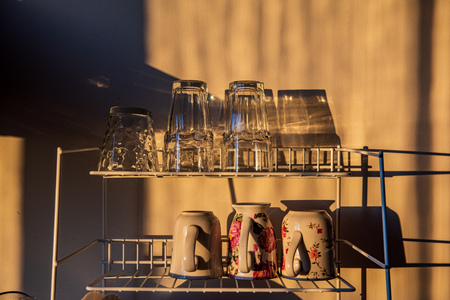 dishes and glasses on a dryer in kitchen in sunset light with shadows and reflections Banco de Imagens - 124877501