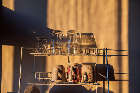 dishes and glasses on a dryer in kitchen in sunset light with shadows and reflections Banco de Imagens - 124877618