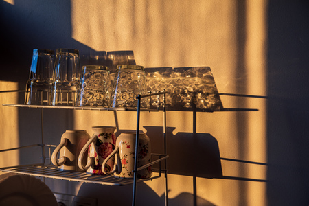 dishes and glasses on a dryer in kitchen in sunset light with shadows and reflections Banco de Imagens - 124877834