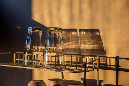 dishes and glasses on a dryer in kitchen in sunset light with shadows and reflections
