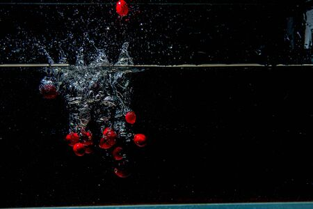 cranberries falling in dark water with splashes in the air Banco de Imagens - 124878145