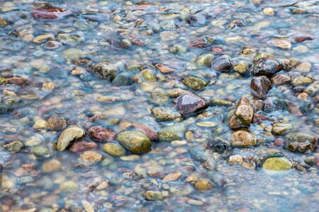 water texture with reflections and rocks on the bottom of stream. nature abstract