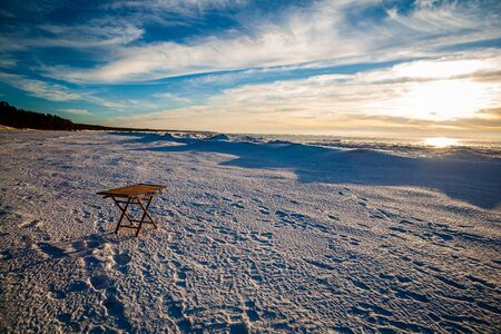 wooden table with coffee on snowy beach by the sea. sunny day