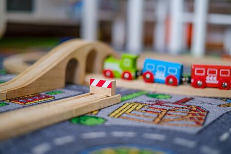baby hands playing and learning with wooden train set on wooden rails on a carpet in nursery at home