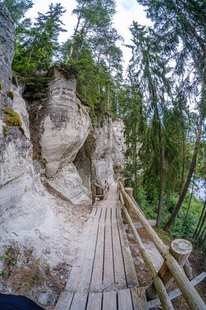 Large sandstone cliffs of Sietiniezis on the shore of the river Gauja in Latvia. tourist nature trail for hiking with wooden stairs