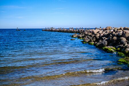 rocky seaside beach with blue water under summer sky and rocks on the shore Banco de Imagens