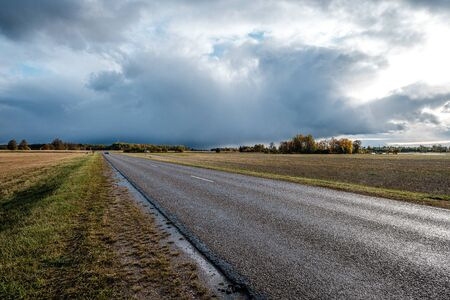 storm clouds over asphalt road in perspective. autumn scene with brand new electricity poles in Latvia 版權商用圖片