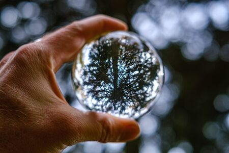 male hand holding crystal glass ball against nature background with reflections in it 版權商用圖片