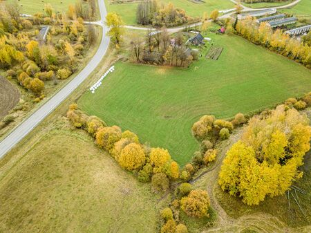 countryside view from above in Latvia with cultivated fields and road network in autumn under dramatic sky