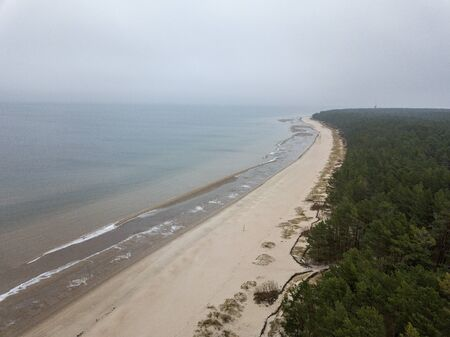 seaside beach with water covered in fog mist. drone aerial image
