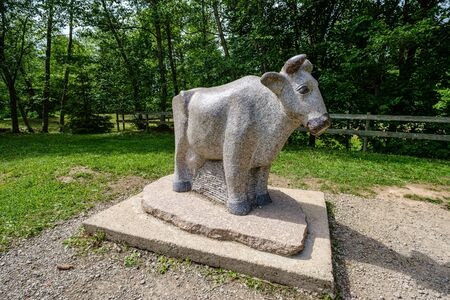 statue of stone cow in park in summer day
