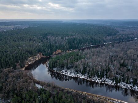 River in winter forest with green trees from above. Aerial drone image of river Gauja in Latvia.