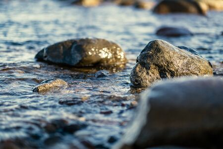 waves crushing on the rocks on beach in sunny day with blue sky and clear water on the sand texture. pebbles