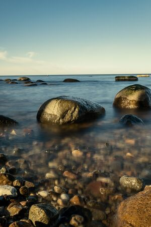sunny beach with blue water and large rocks in the sand. Latvia under clear sky
