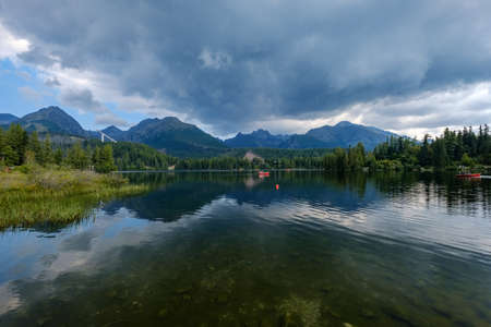 autumn nature reflection in lake of Strbske Pleso in Slovakia surrounded by trees and mountains 新聞圖片