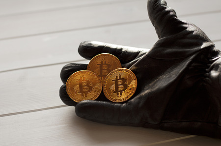 A gloved hand offers payment in gold bitcoins Stock Photo