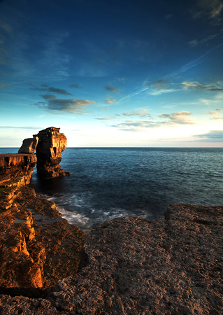 Rocky coastal shot with sun setting after warm day Stock Photo