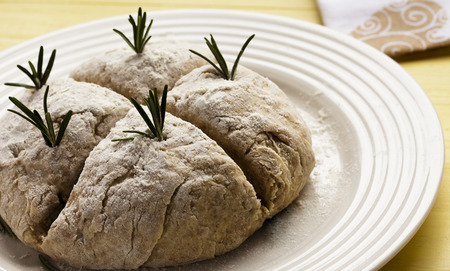 Baker slices four score into freshly made Irish Soda Bread for St Patricks Day. Inset with Rosemary Herbs