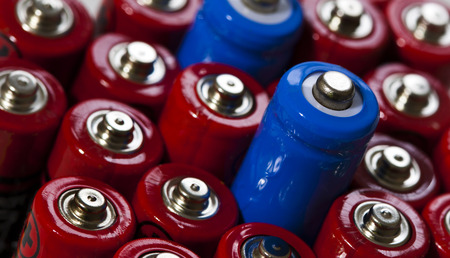 Stacked double A batteries with two batteries peaking out of pile