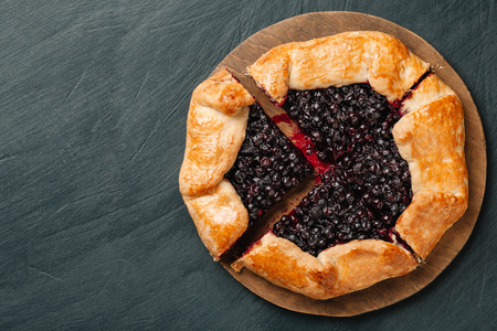 Cutted galette with seasonal berries. Flat lay crispy summer berry pie on a gray-blue background with copy space.