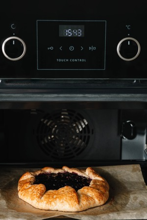 Closeup photo of galette with black currant baking in a hot oven
