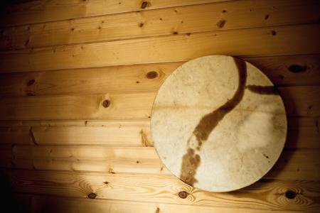 Pandereta de madera vieja colgada en la pared de madera blanca.