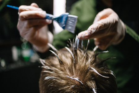 Hairdresser in gloves with a brush to apply hair dye. Coloring in the barber shop