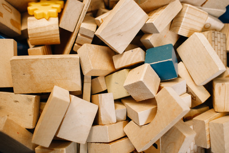 Toys in kindergarten. Chaotically scattered wooden blocks of beige color Banque d'images - 122900924