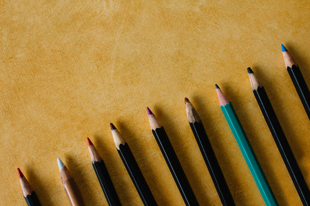 Colored pencils on a textural paper background of yellow color with copy space